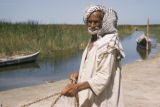 Iraq, man standing near river holding net