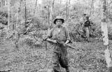 Malaysia, communist Gurkha soldiers carrying another on jungle patrol