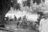 Indonesia, men sitting at table at outdoor restaurant in Borobudur