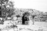 Israel, woman filling container at cistern in Bethlehem