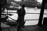 Hong Kong, woman carrying child on back at pier