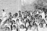 India, girls and Caucasian woman gathering to pose at school in Amalner