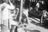 Indonesia, girl selling food to woman at market place in Tegal