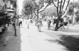 Myanmar, busy street with pedestrians and rickshaws in Rangoon