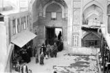 Iraq, view of men walking through entrance of mosque in Karbalā'