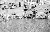 India, people resting under parasols at ghat on Ganges River in Varanasi