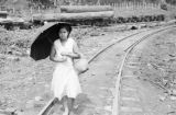 Philippines, woman with umbrella walking on railroad track in Kolambugan