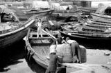 Singapore, men loading rubber onto barge in Singapore