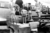 Laos, men unloading American-made flares from airplane
