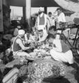 India, customers examining produce at market in Delhi