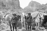 Jordan, portrait of armed Arab guards with horses in Petra