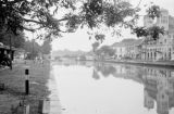Indonesia, view of canal with bridge in distance and buildings alongside in Jakarta