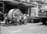 Hong Kong, pedestrians watching men transporting cable reel in Victoria