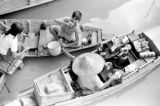 Thailand, man and children with cookware on boats