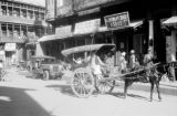 India, Shrinagar street scene with retail stores and passing wagon