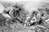 Laos, soldiers cooking rations around fire in Xiangkhoang