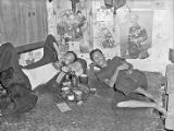 Singapore, men smoking in opium den