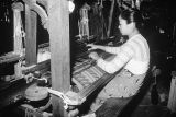 Myanmar, woman weaving silk at loom in Mandalay