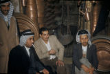 Baghdad (Iraq), four men gathered in metal workshop