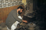 Baghdad (Iraq), man in shop stoking fire with tongs