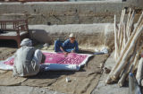Baquba (Iraq), man and boy rolling up quilt laid out on ground