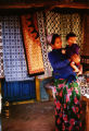 Pokhara (Nepal), woman holding a child with textiles in the background
