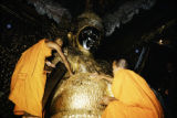 Thailand, buddhist monks gilding statue with gold leaf