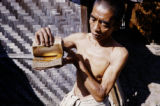 Myanmar, man looking at sheets of gold leaf