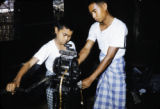 Myanmar, young men using an extruder to make gold leaf