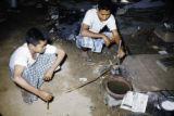 Myanmar, men extruding gold to make gold leaf