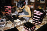 Myanmar, man applying gold leaf to book covers