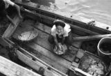 Vietnam, woman washing dishes on a boat