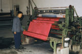 China, worker operating silk textile machinery at factory in Yan'an