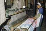 China, worker operating loom at silk textile factory in Yan'an