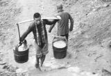 Chongqing (China), boy carrying water in buckets with a yoke