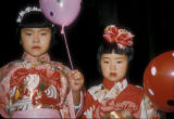 Kobe (Japan), two girls in kimonos holding balloons in a festival