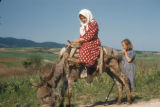 Turkey, girl riding a donkey on the road to Yalova