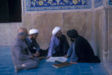 Esfahan province (Iran), four seated men reading and talking