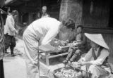 China, American soldier, possibly George Clements, at outdoor market