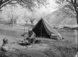 China, man cooking in front of tent