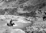 China, man on horse crossing river
