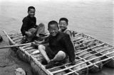 Lanzhou (China), portrait of boys sitting on an inflatable sheepskin raft