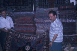 Tehran (Iran), two men displaying rugs in shop