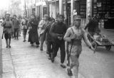 China, soldiers and townspeople walking through a business district