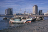 Bombay, boats on shore with high rise buildings in background