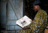 Lagos, man reading English-language newspaper