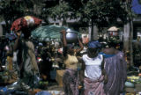 Abidjan, busy market with people carrying goods