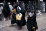 Dar es Salaam, Muslim women carrying children in street
