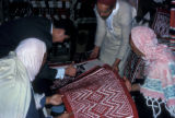 Nefta, rug merchant and assistants cutting weaving on rugs
