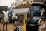 Accra, woman carrying sugar cane